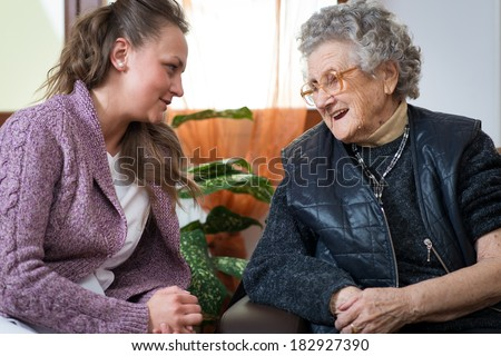 Old woman with her home caregiver - stock photo