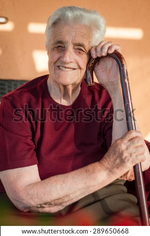 Old woman with her stick - stock photo