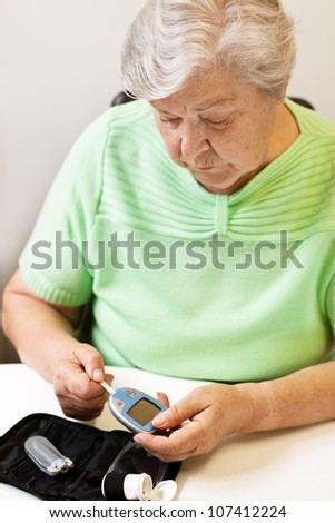 old woman with test strip and blood glucose meter - stock photo