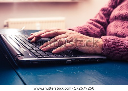 Old woman working on laptop computer at home - stock photo