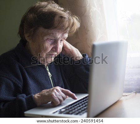 Old woman works (learning to work) on laptop in her house. - stock photo