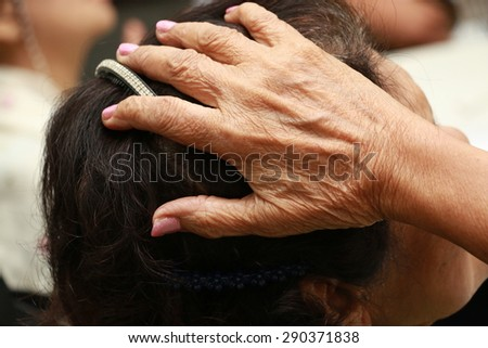 old women put her hand on her head - stock photo