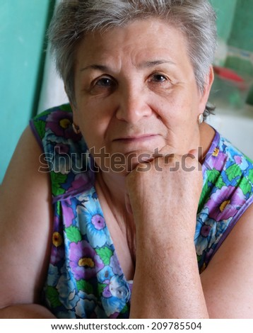 Old women thinking indoors with her hand on chin - stock photo