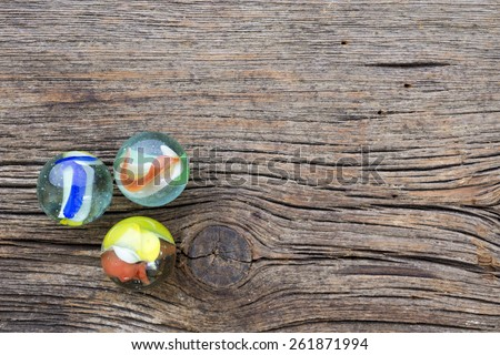 Old wood background with three glass marbles.