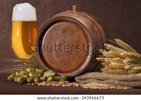 old wood barrel with beer glass, hops, wheat, grain, barley and malt