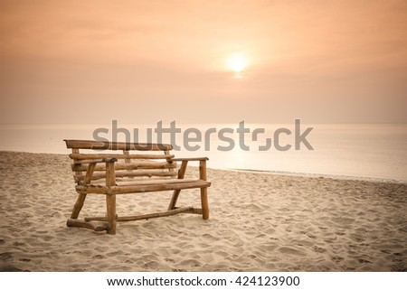 old wood bench on the beach with sunrise background - stock photo