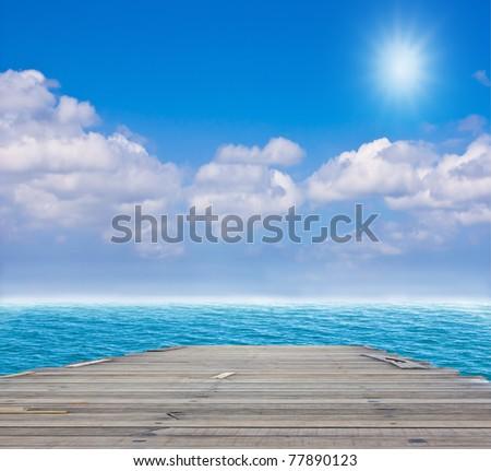 old wood bridge to blue sea - stock photo
