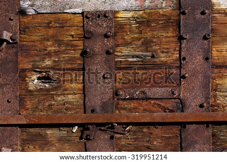 Old wood door construction with vintage forged iron plates. Weathered and rusted - stock photo