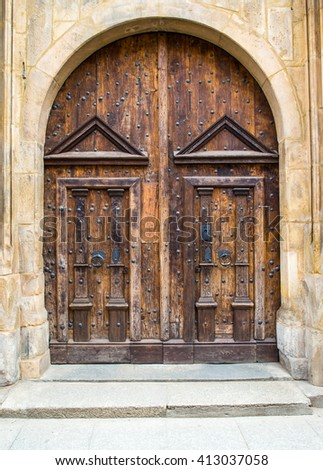 Old wood doors, gate to the church or castle, surrounded by stone wall - stock photo