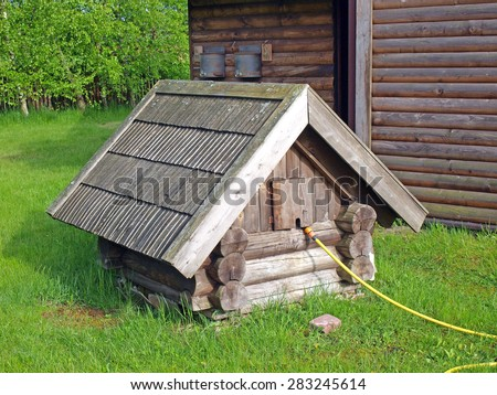 Old wood log well with shingle roof on yard         - stock photo