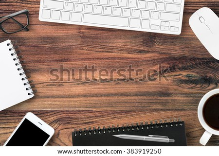 Old wood office table with office supplies on top. Top view with copy space in the middle. Youngster office life concept. - stock photo