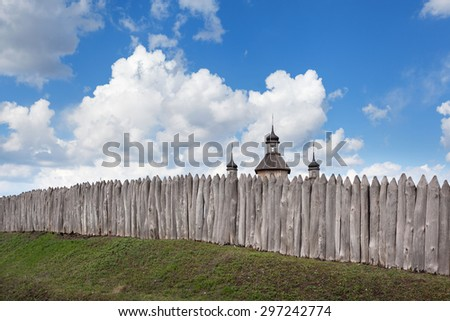 Old wood rustic church building and wooden fence against blue sky at sunset - stock photo
