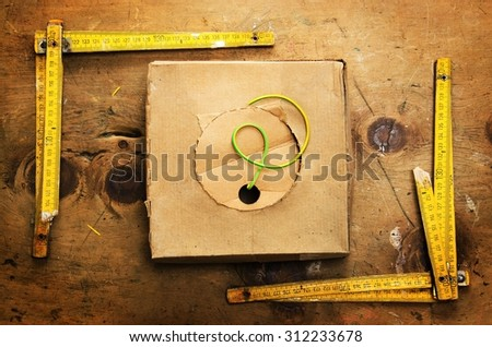 Old wood table with two yardsticks and box with wire in rustic vintage style. Top view. Retro concept background.  - stock photo