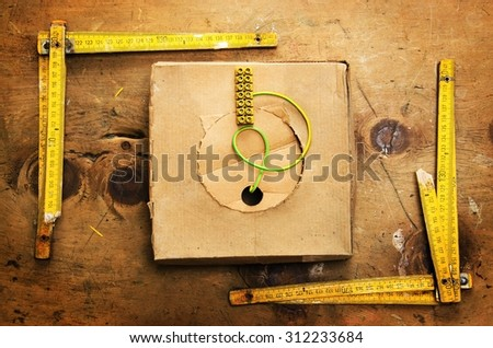 Old wood table with two yardsticks, box with wire and screw terminal in rustic vintage style. Top view. Retro concept background. - stock photo