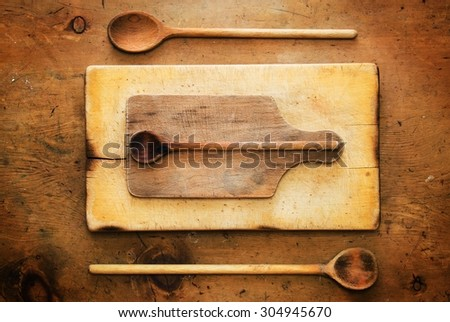 Old wood table with wooden spoons and boards in rustic vintage style. Top view. Retro concept. - stock photo