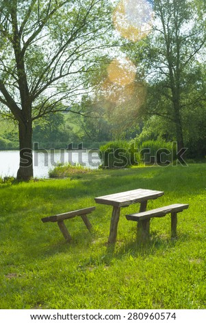 old wood trunk table and benches on river bank, focus on table - stock photo