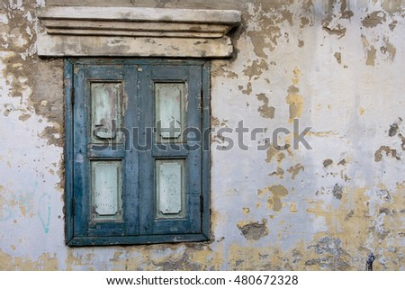 Old wood window in blue color on old wall.
