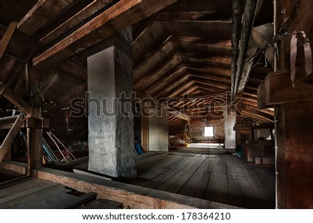old wooden attic with roof framework structure and window - stock photo