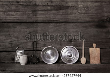 Old wooden background with miniatures of kitchen utensils like pots, spoon of wood, can and others. - stock photo