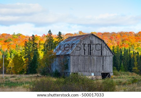 Old wooden barn against colorful trees