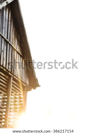 Old wooden barn and the sun - stock photo