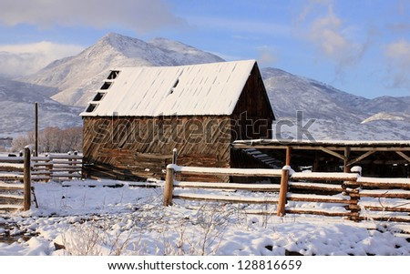 Old wooden barn with fresh snow in the rural Utah, USA.