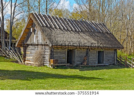 Old wooden barn with thatched roof and two doors on Hiiumaa island old farm, Estonia