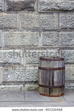 Old wooden barrel in front of a stone wall