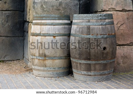 Old wooden barrels against a wall - stock photo