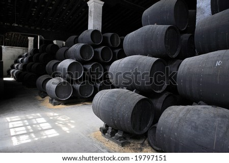 old wooden barrels of sherry in bodega of Spanish town of Jerez de la Frontera - stock photo