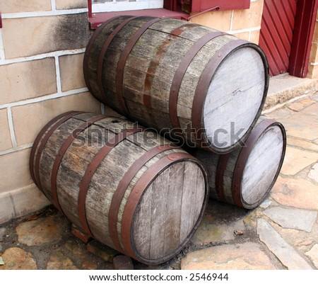 Old wooden barrels on the sidewalk. - stock photo
