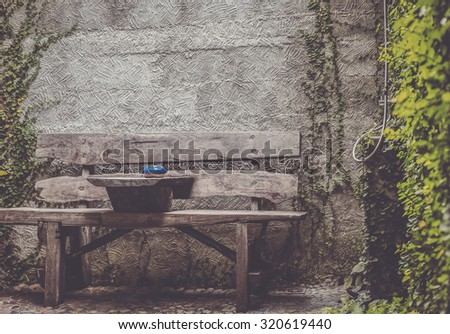 Old wooden bench in the garden and stone wall. - stock photo