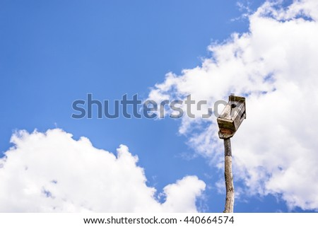 Old wooden birdhouse on a wooden post on the background of beautiful blue sky and clouds