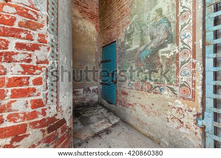 Old wooden blue door to the abandoned bell tower. Partially preserved ancient temple old Russian painting - stock photo