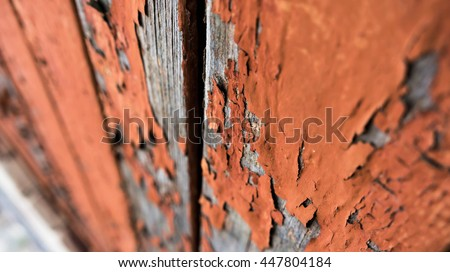 old wooden boards are painted with yellow and orange tones paint, have peeled off under the influence of an environment,