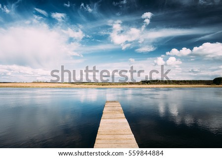 Old Wooden Boards Pier On Calm Water Of Lake Or River At Evening Or Morning Time. Forest On Other Side. Landscape. Nature Background.