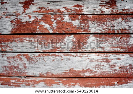 Old wooden boards with the exfoliating red paint, closeup horizontal
