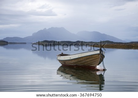 Old wooden boat anchored at sea at gray day. Photographed at Helgeland coast in Nordland county, Norway. - stock photo