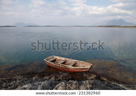 Old wooden boat at Helgeland archipelago at Norwegian coast. Mountains Donna and Syv Sostre at the horizon.