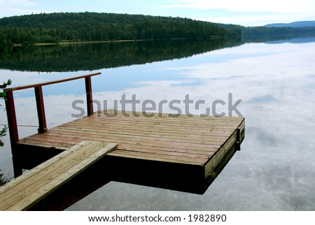 Old wooden boat dock on a beautiful lake in the evening