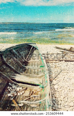 Old wooden boat on the seashore, vintage styled aged photo. - stock photo