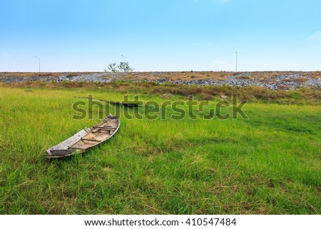 Old wooden boat trees in a sunny field in spring - stock photo