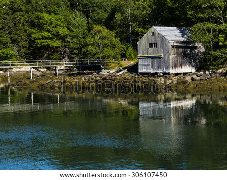 Old wooden boathouse in Maine harbor.