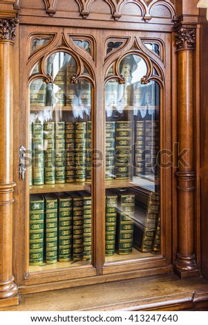 Old wooden bookcase with the books of the nineteenth century - stock photo