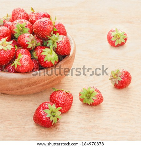 Old Wooden Bowl Filled With Succulent Juicy Fresh Ripe Red Strawberries On An Old Table top - stock photo