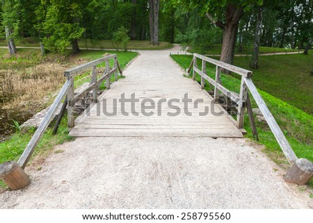 Old wooden bridge and walking lane in park, Trigorskoye village, Russia - stock photo