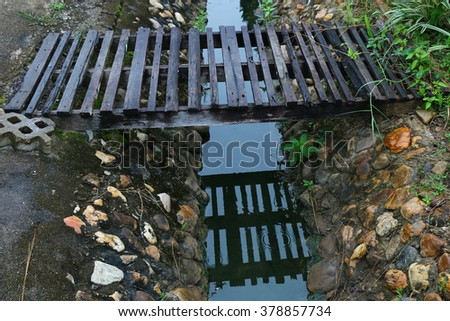 Old wooden bridge crossing a ditch