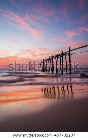 Old wooden bridge in the sea with sky sunset