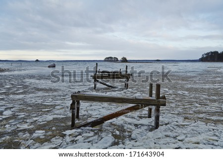 Old wooden bridge on the lake in wintertime - stock photo