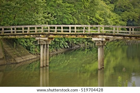 Old wooden bridge over river in a park with green background